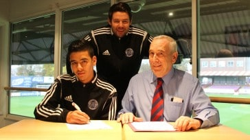 Jay Welch signs his contract watched by Scott Harrison and Bob Green