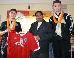 Striker Ashley Bayliss (left) and Captain Ben Hutchings (right) present a signed ATFC shirt to Sahara Club President Bir Bhadra Acharya